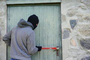 Einbrecher versucht eine Tür aufzubrechen - eine Alarmanlage kaufen hilft